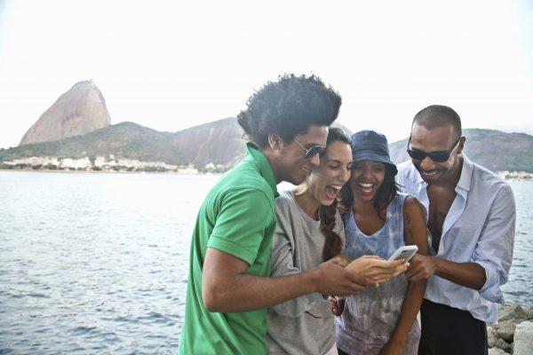 Four friends looking at smartphone, Rio de Janeiro, Brazil